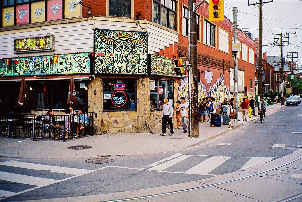 A daytime photo of the exterior of Sneaky Dees at College and Bathrust.