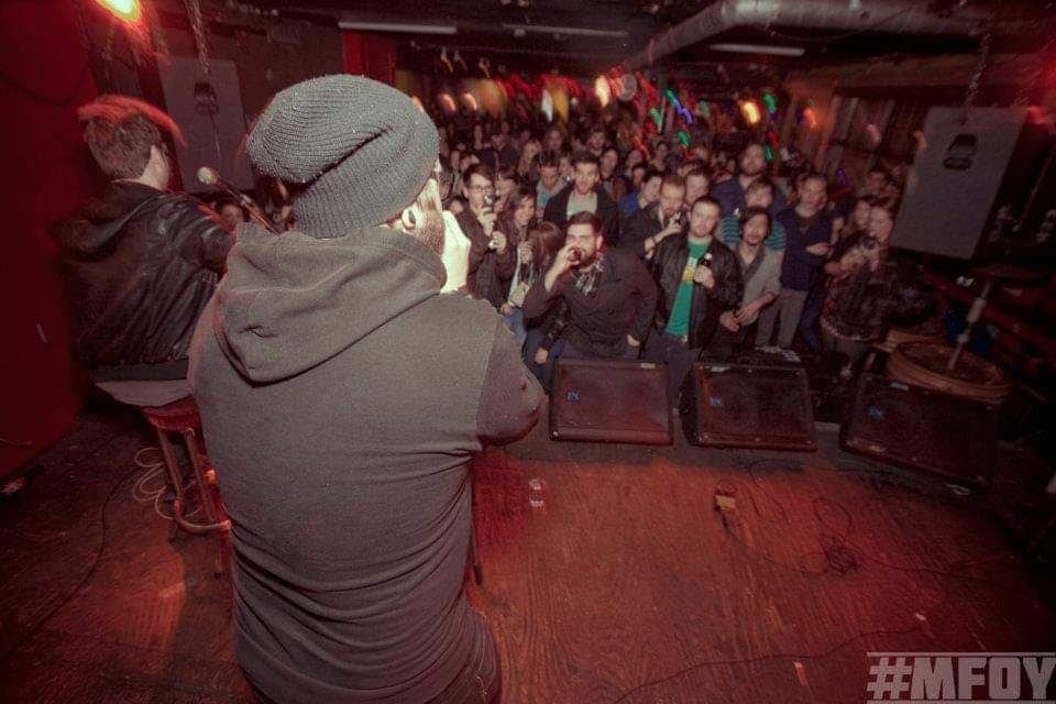 Artist Tommy Dillon faces a crowd of fans from the stage at Sneaky Dees