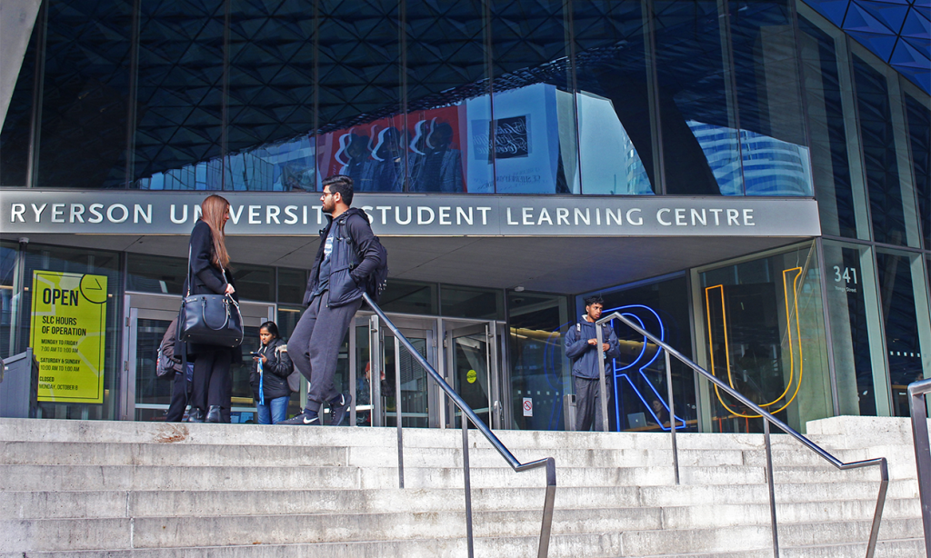 students stand outside of the steps of the Sheldon and Tracy Student Learning Centre
