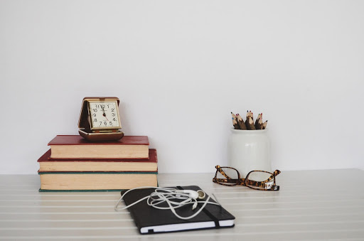 a pair of glasses, a plant and some books on a white desk
