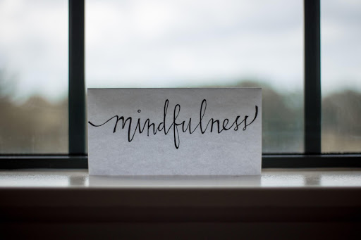 a sheet of paper with the word mindfulness written in black ink perched on a window sill