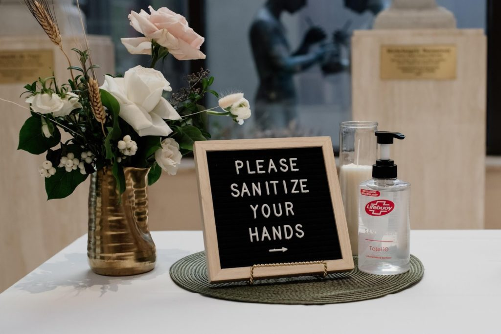 """a board that says """"Please sanitize your hands"""" on a table used at weddings with flowers and hand sanitizer surrounding the board"""
