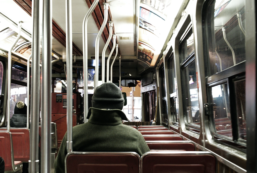a view from inside a train with a person sitting facing away from the camera sitting on red seats