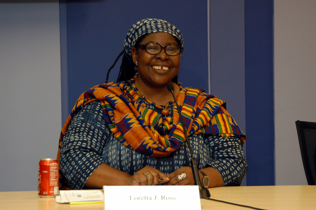 a woman with glasses sits at a brown desk smiling straight ahead