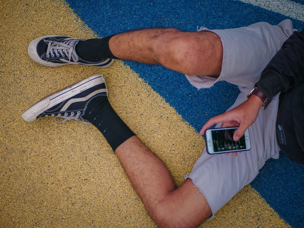 a shot of a man's hairy legs sprawled across the floor with a phone in his hand