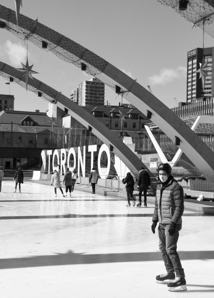 a man skates with his mask on near the 'Toronto' sign