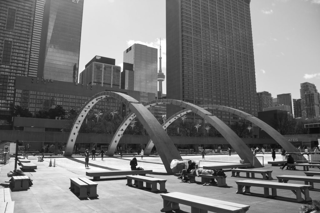 a black and white image of the arches at nathan phillips square over the ice rink with some people skating on it