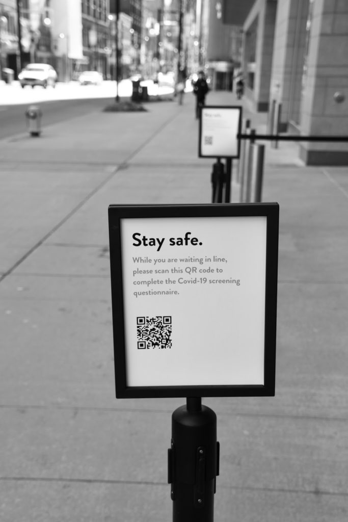 a sign with a QR code outside Nordstrom that prompts potential shoppers to take a COVID questionnaire before entering the store. it is attached to a stanchion.