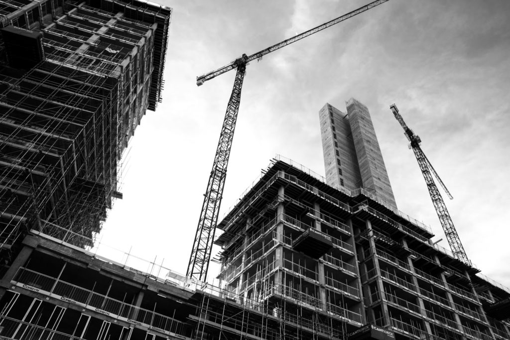 A black and white image of buildings under construction and a large crane in the sky