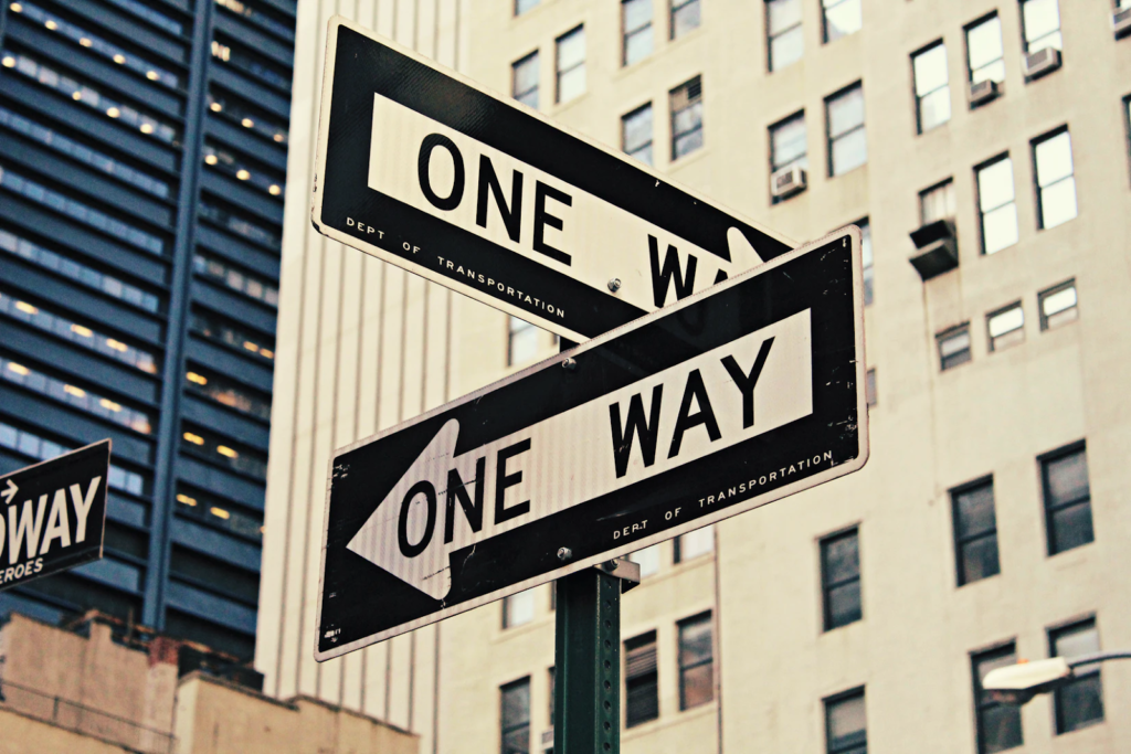 """a street sign that says """"One Way"""" on it"""