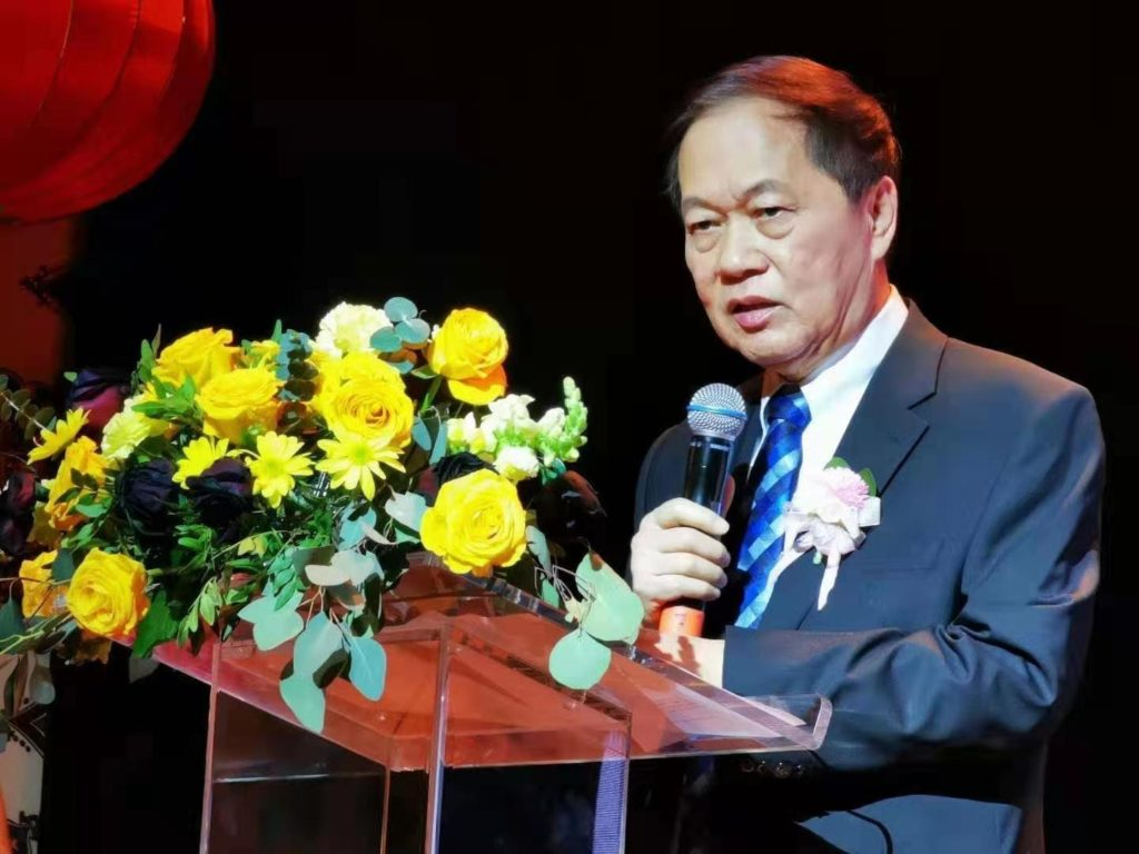 an elderly man dressed in a blue suit and tie stands in front of a podium with yellow flowers and speaks into a mic