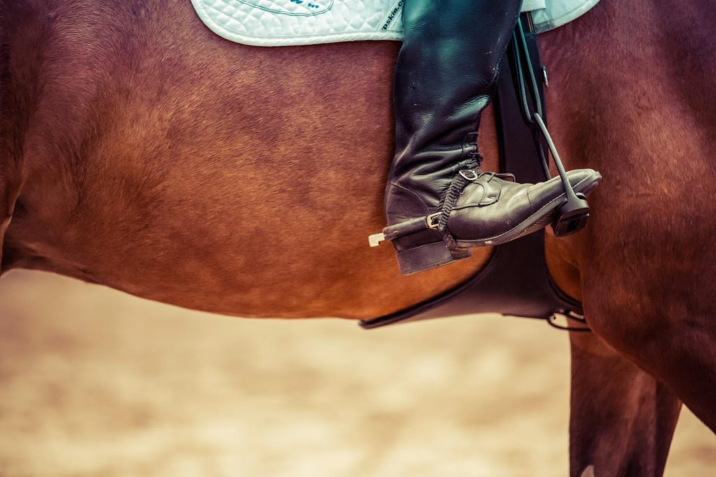 a closeup shot of someone's boot while they are on a horse in a saddle