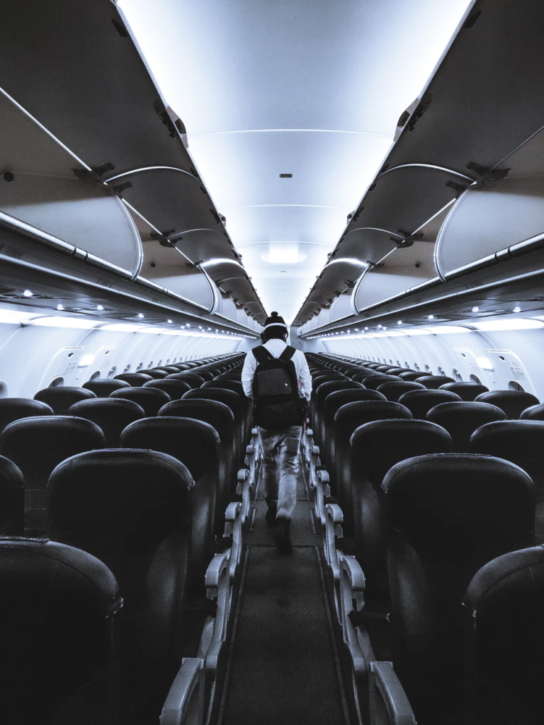 a view from the middle of an airplane aisle with rows of black and gray seats on the left and right sides and a traveller with a backpack walking away from the camera