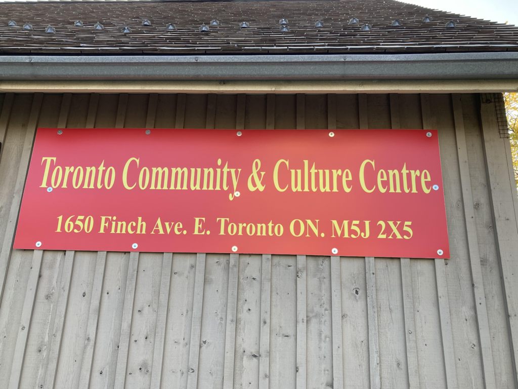 """A red sign on a wooden wall with the phrase """"Toronto Community and Culture Centre at 1650 Finch Avenue East"""" written in gold"""