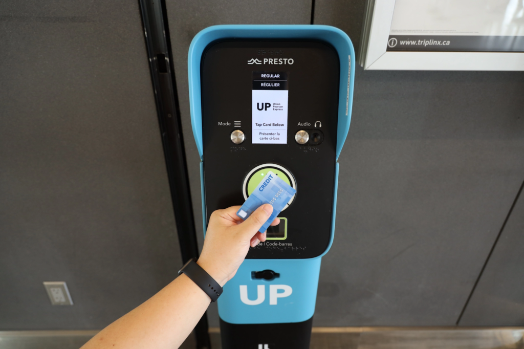a person taps their card on a machine for fare collection