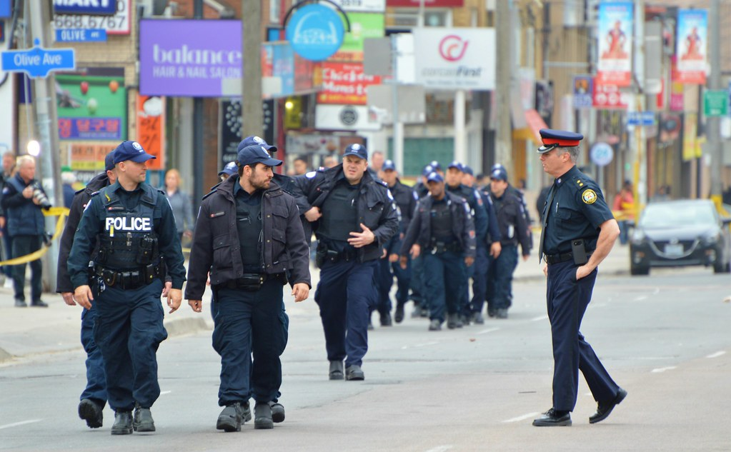 a group of policemen walk on an empty street that's been cleared of pedestrians and cars after a van drives into a crowd in Toronto