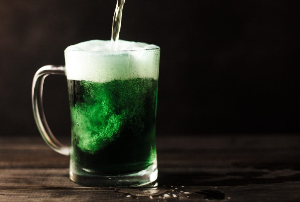 liquid is poured into a green alcoholic drink in a mug on a dark wooden table