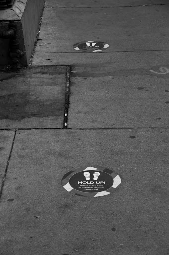 a sticker on the ground with two feet reminding people to stay 6 feet apart