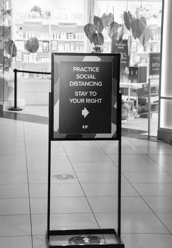 a sign inside a mall that reminds shoppers to socially distance