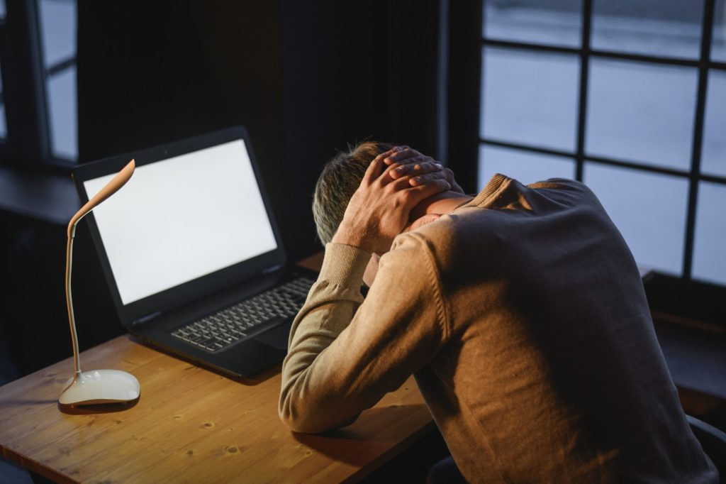 a man sits at a desk in front of his computer with his head in his hands