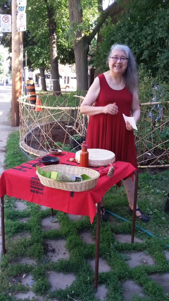 a woman in a red dress stands on some grass with a table with baskets on top