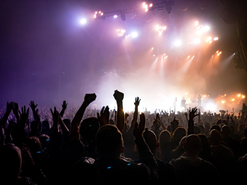 a silhouette of a huge crowd at a concert with their hands up