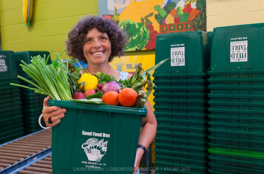 a woman holds a green box filled to the brim with vegetables and other produce