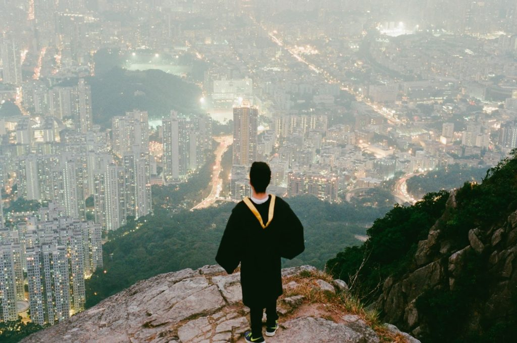 a boy wearing a cap and gown stands on a cliff looking out at the city