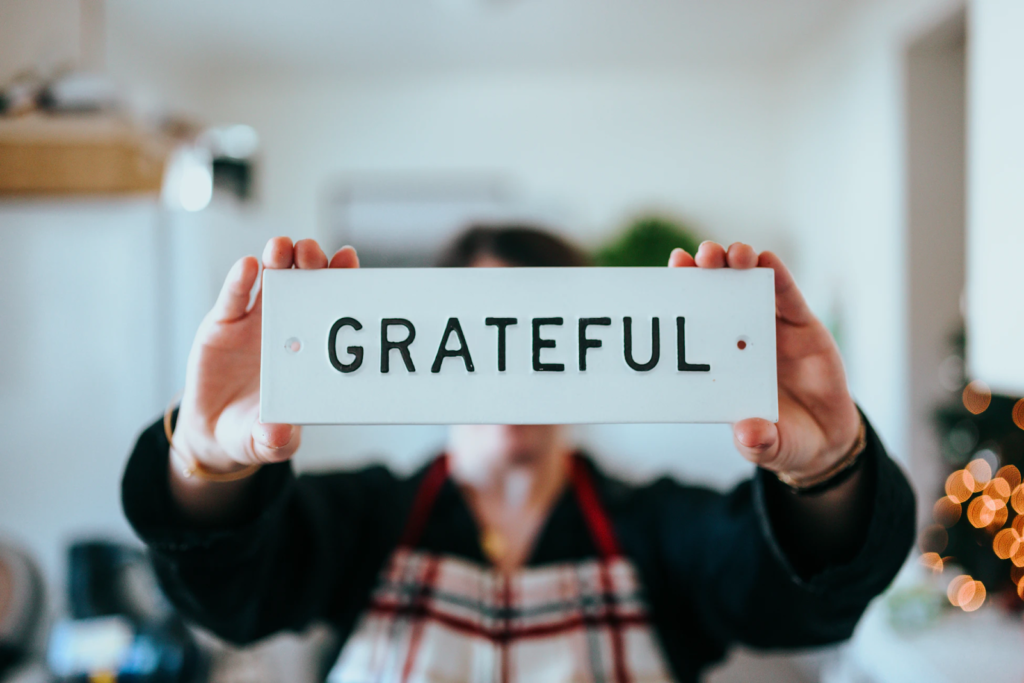 a person holds a sign that says grateful in front of their face to the camera