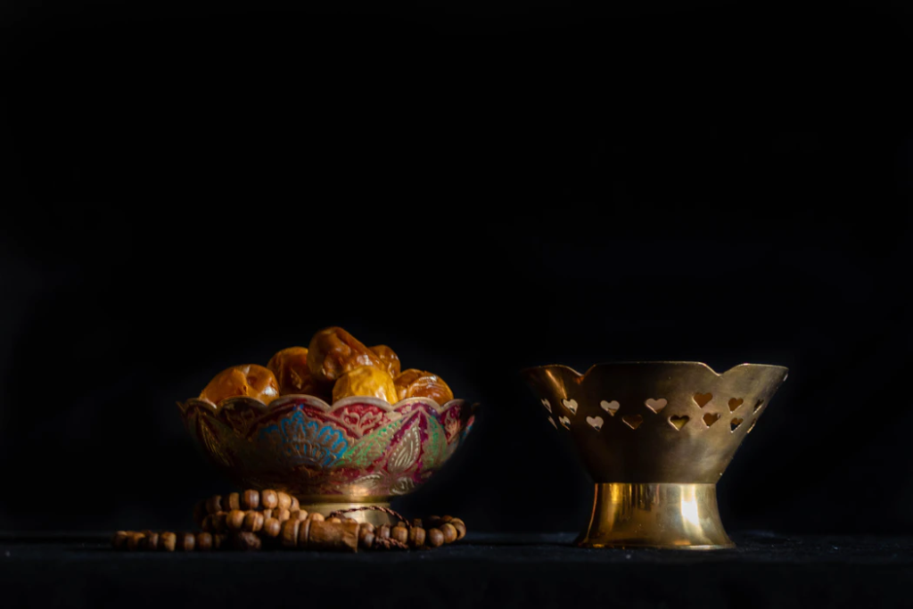 two golden bowls with sweets inside are side by side on a black table
