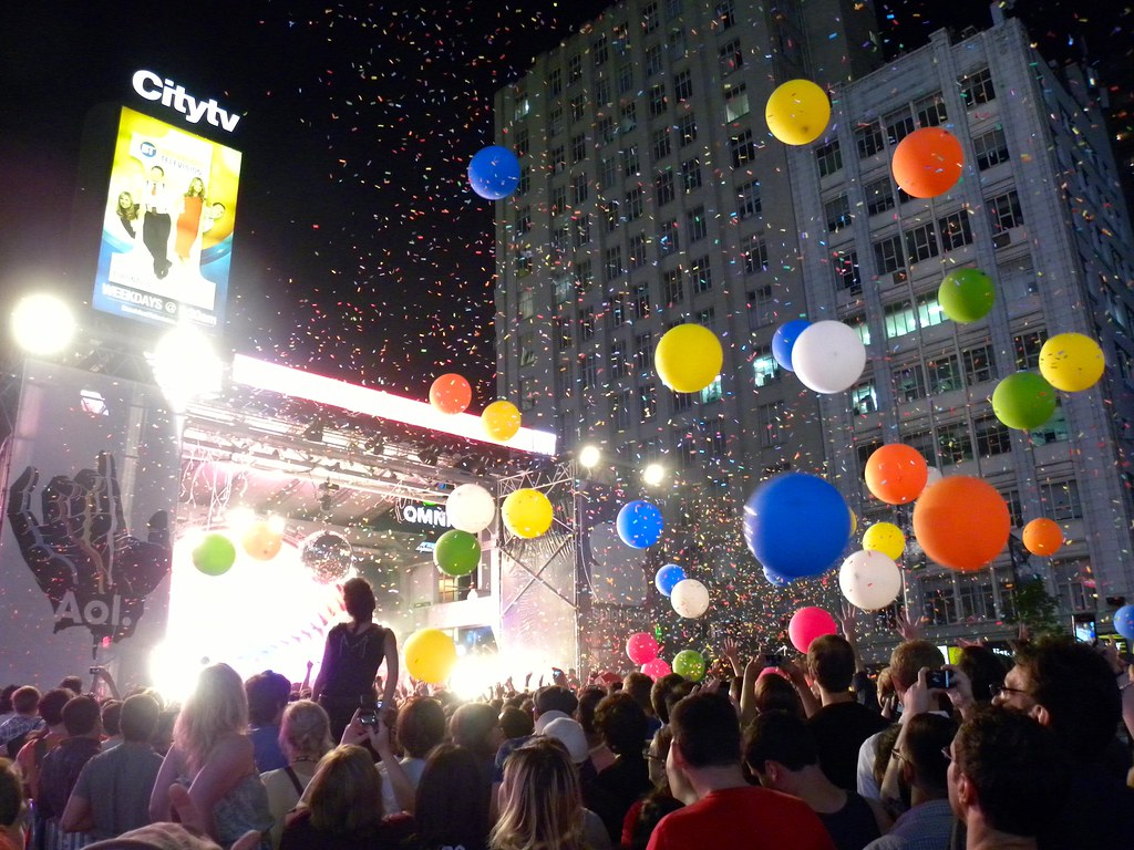 a crowd of people are at a concert at night time with balloons flying around in the air