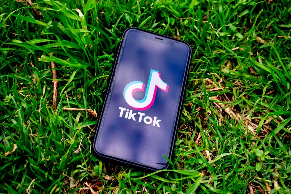 an iphone on some grass with the tiktok app open on it