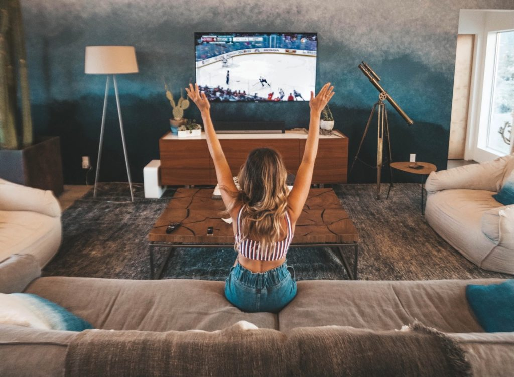 a woman puts her hands up as she sits on a couch looking at a tv screen with a hockey game on it