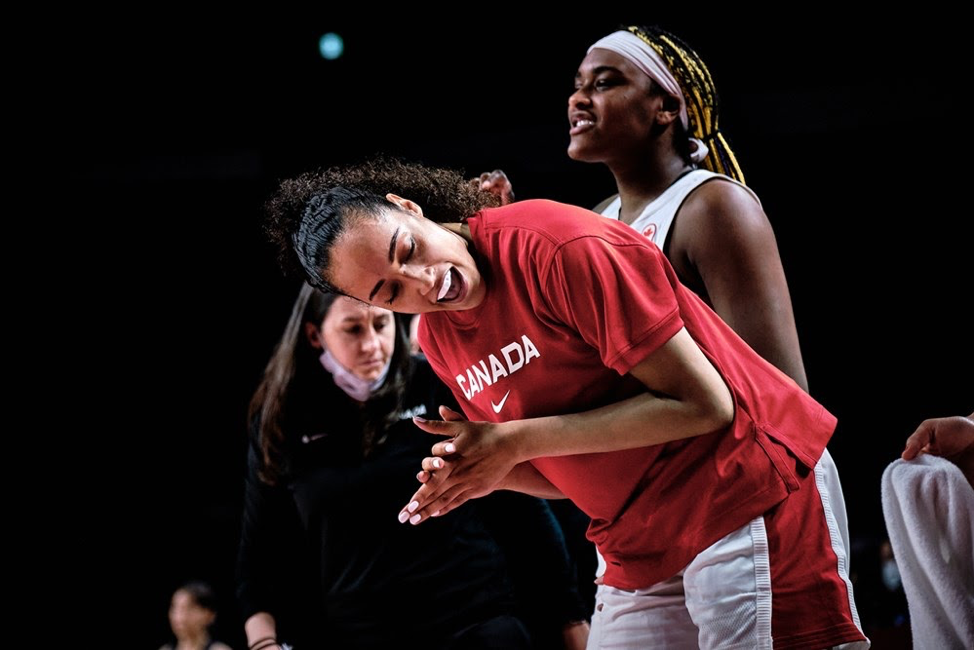 Two women basketball players in foreground, coach Carly Clarke in background