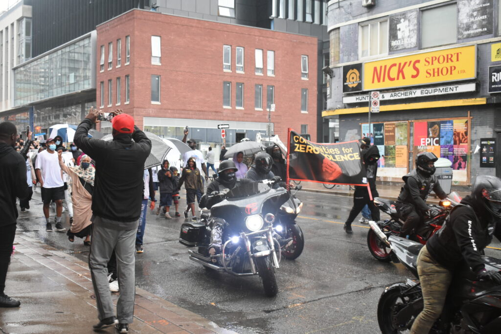 Bikers and people walking down a street. They hold signs protesting gun violence.